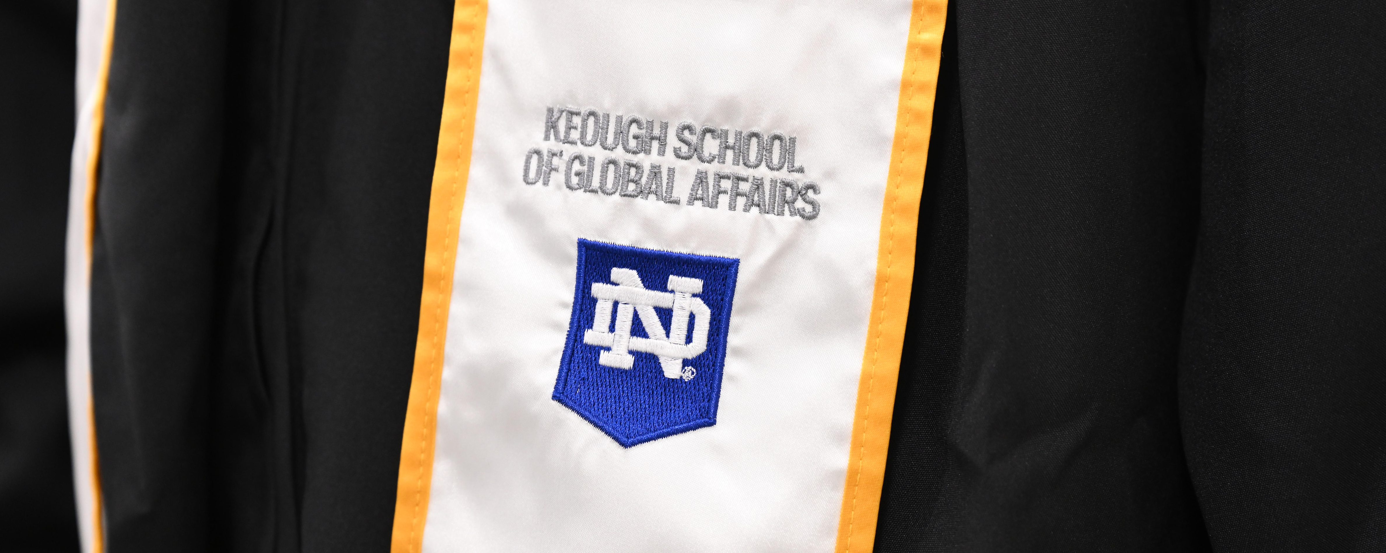 A white stole with gold trim and the Keough School logo