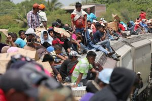 Immigrants ride on the top of a freight train in Mexico