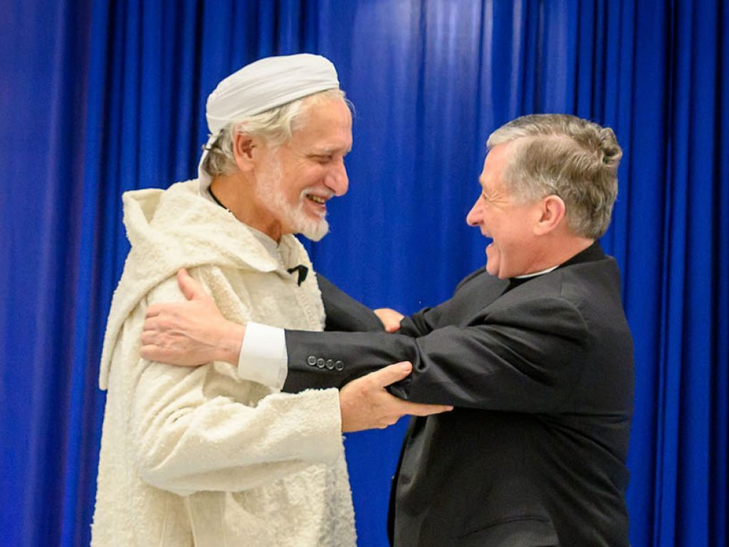 """November 20, 2019; (left to right) Daoud Casewit, President of the American Islamic College, Cardinal Blase J. Cupich, Archbishop of Chicago, share a hug after a discussion hosted by the Keough School of Global Affairs called """"Commemorating the Sultan and the Saint: A Christian-Muslim Dialogue,"""" in the Nanovic Forum. (Photo by Matt Cashore/University of Notre Dame)"""