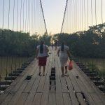 Women in Colombia walk across a bridge together