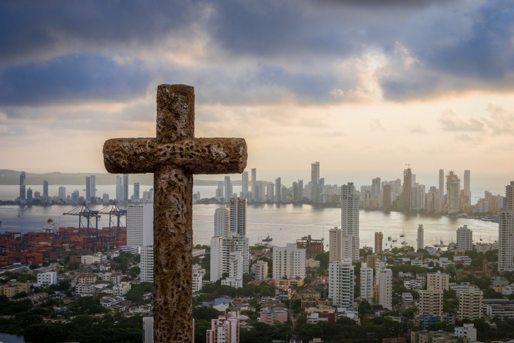 A cross looking over a bustling city. A cross overlooking Cartagena, Colombia.
