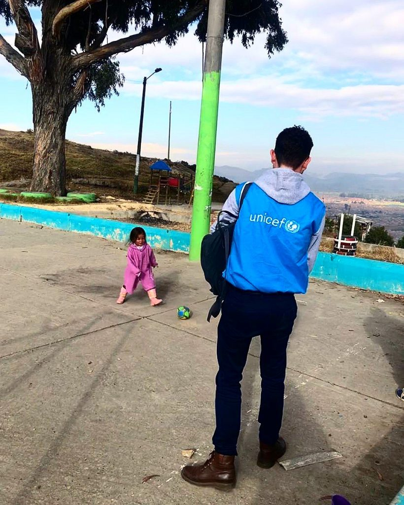 Juan wearing a bright blue UNICEF jacket, watches a child play with a soccer ball.