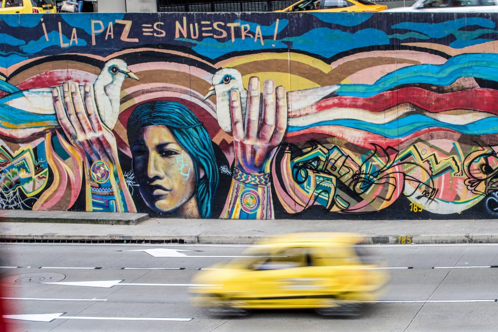 Colorful graffiti on a wall next to a highway. A woman is holding up two doves and a saying above her says 'Peace is Ours'.