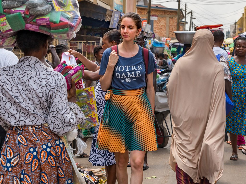Notre Dame student walks through an outdoor market in Ghana