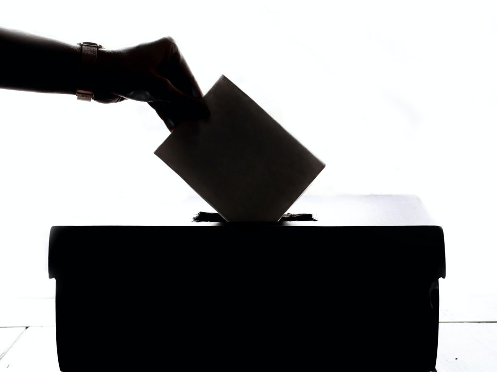 Black and white photo of hand dropping voting ballot into a box