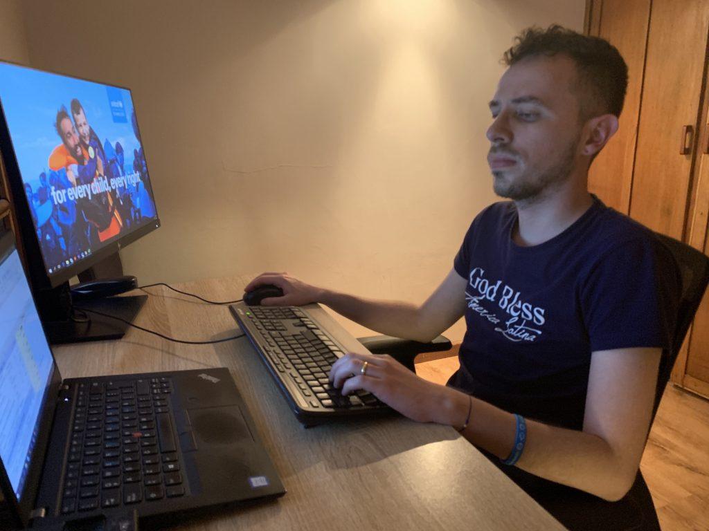 Juan sits at his computer desk.