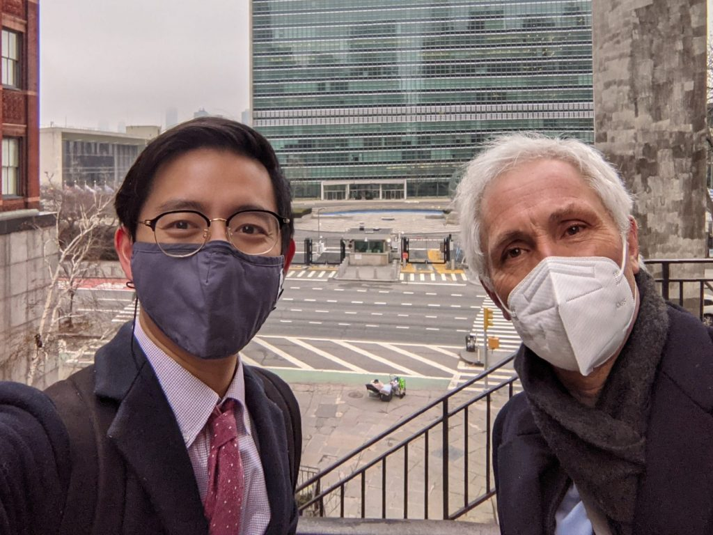 MGA graduate Derek Lee stands in front of UN headquarters with his supervisor from the Mennonite Central Committee.