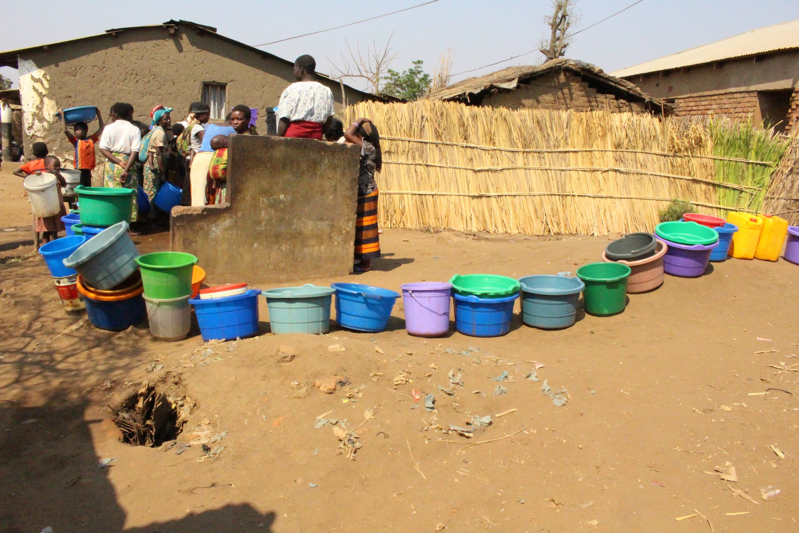 Women and girls stand near a line of colorful plastic water buckets outside a well in Lilongwe, Malawi