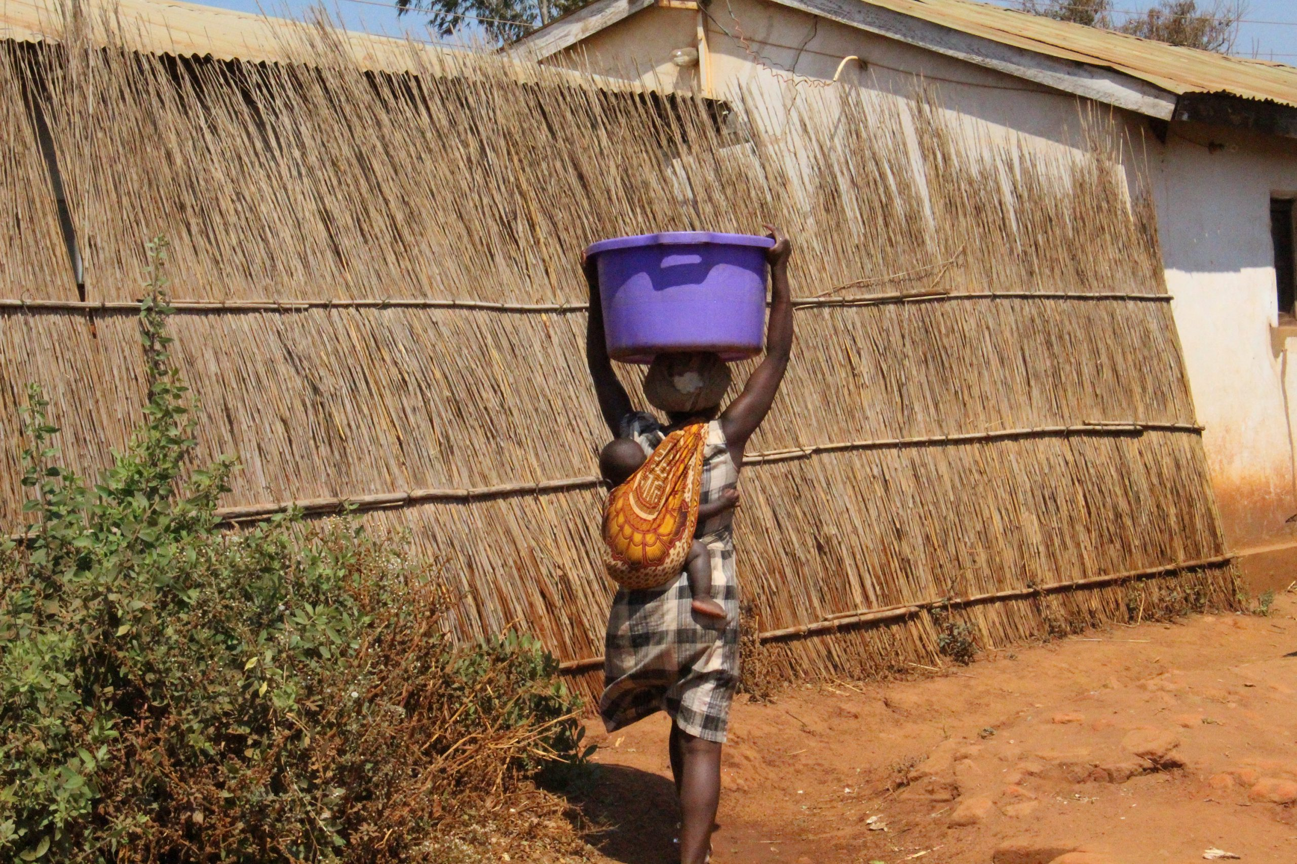 Woman in Malawi carrying bucket of water on her head while carrying a baby on her back.