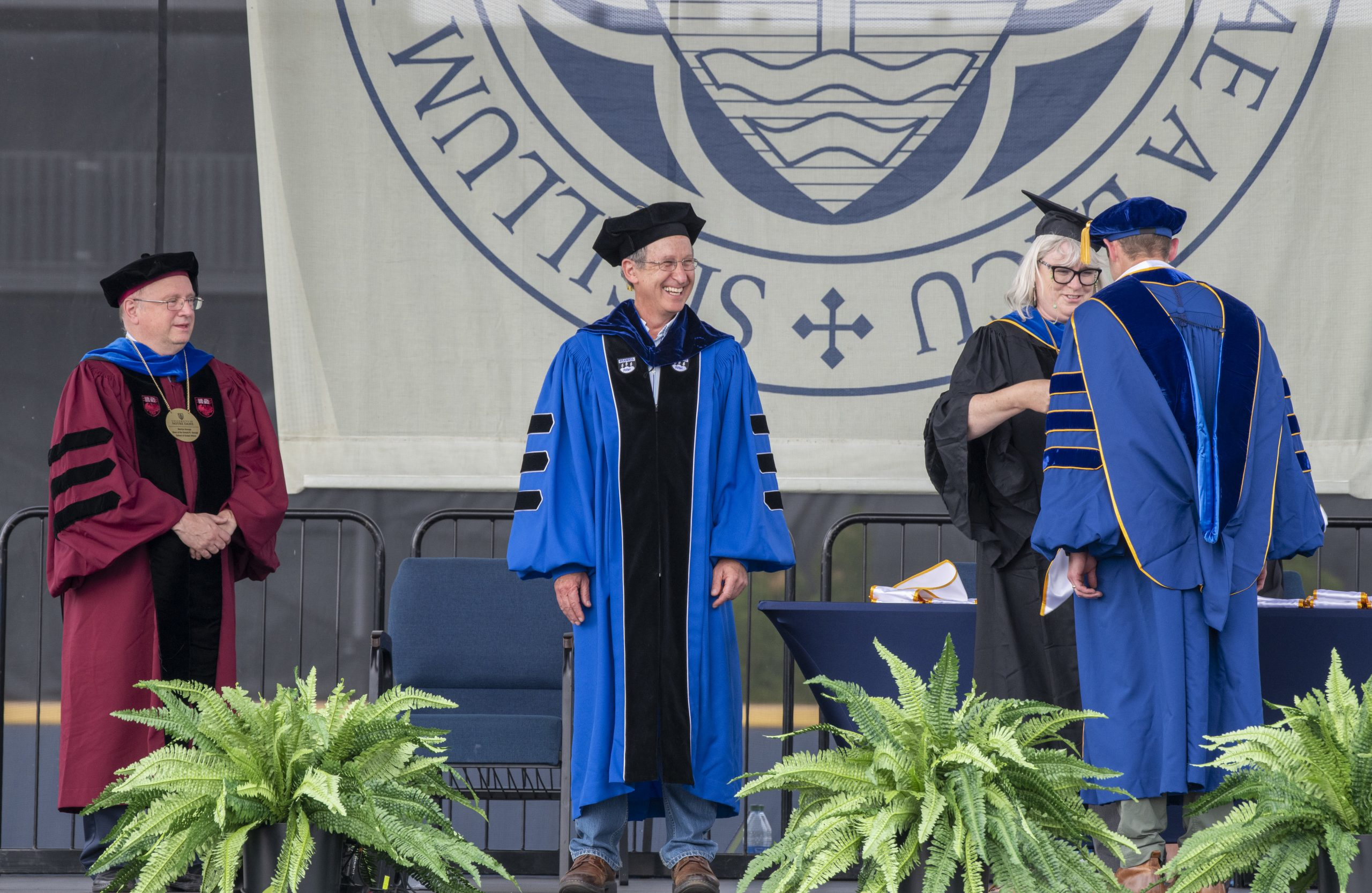 PhD student Drew Marcantonio receives his graduation stole on stage.
