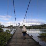 Colombian walking across a bridge over water