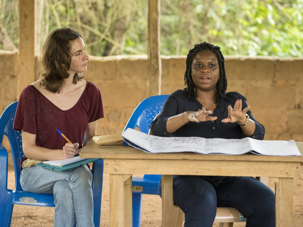 female student sitting next to a woman speaking