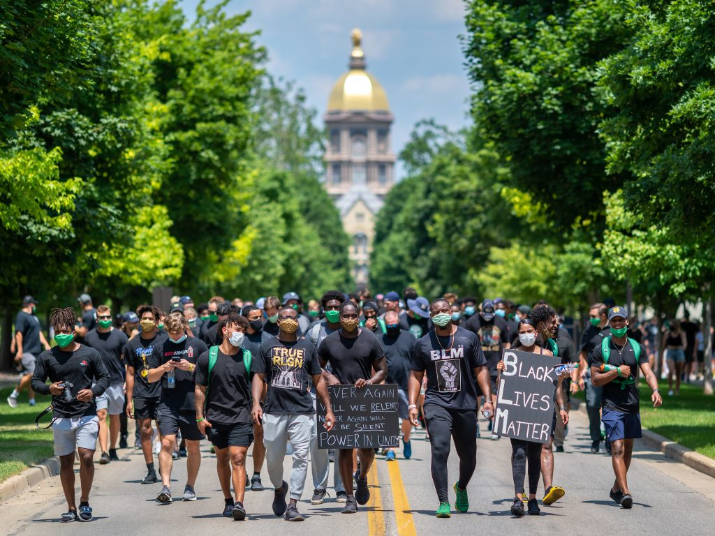 Members of the Notre Dame football team lead participants on a walk through campus in recognition of Juneteenth.